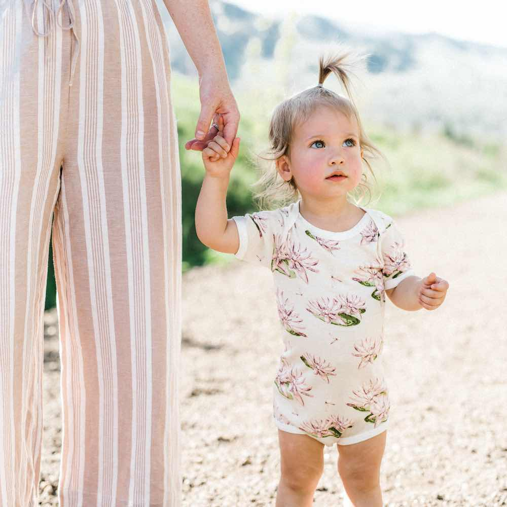 Mom Holding the Babies Hand Wearing Bamboo One Piece or Onesie in the Water Lily Print by Milkbarn Kids