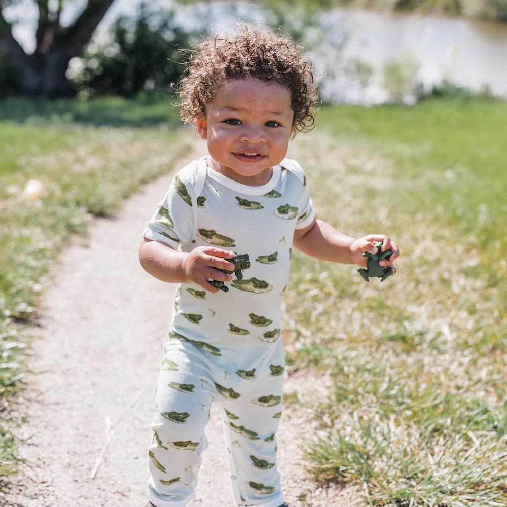 Little Baby in a Path in Front of a Lake Wearing a Bamboo Romper or Jumpsuit in the Leapfrog Print by Milkbarn Kids