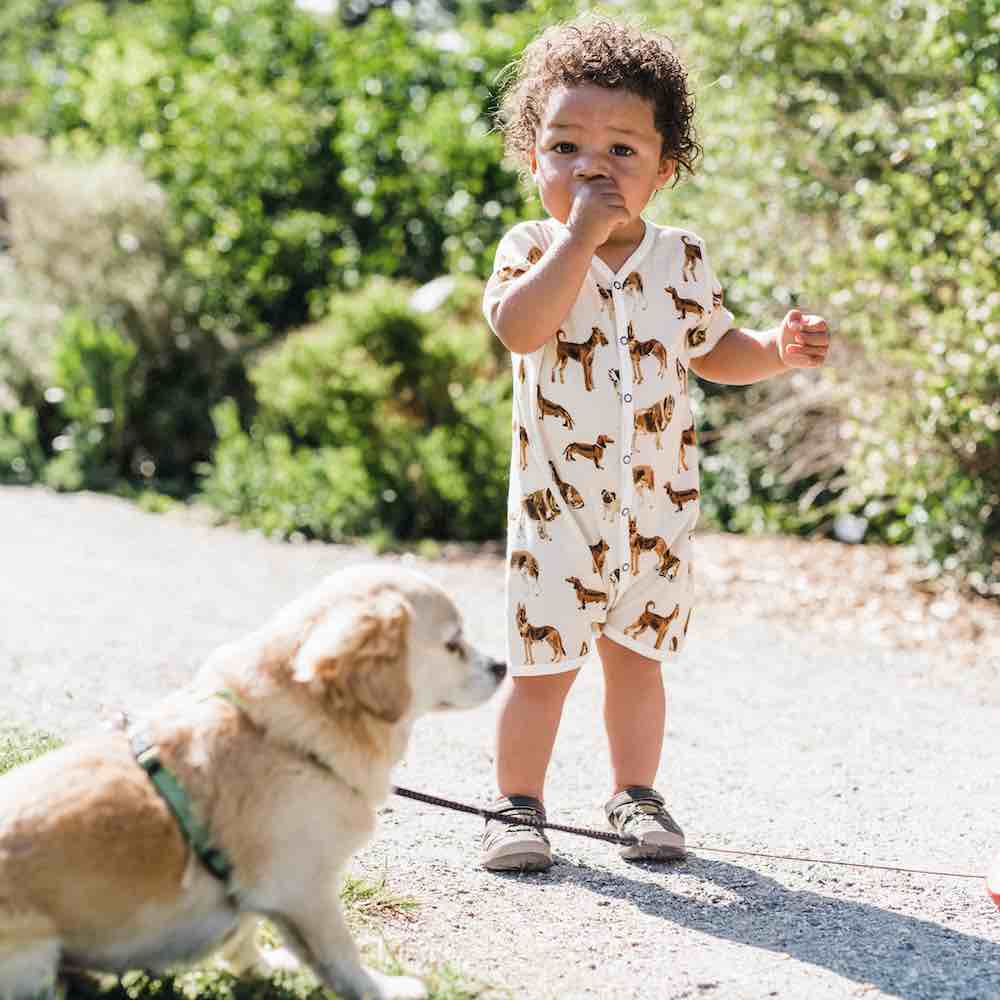 Dog and Little Baby Boy Wearing an Organic Cotton Shortall or Jumpsuit in the Natural Dog Print by Milkbarn Kids