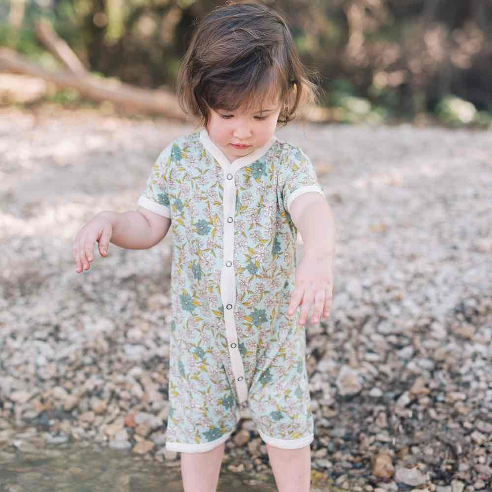 Little Girl Playing in the River Wearing a Bamboo Shortall or Baby Playsuit in the Blue Green Floral Print by Milkbarn Kids