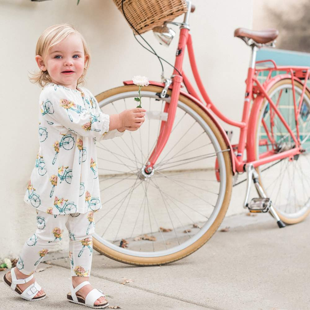 Baby girl next to a pink bicycle wearing Milkbarn Kids bamboo Dress and Legging Set in Bamboo Floral Bicycle Print
