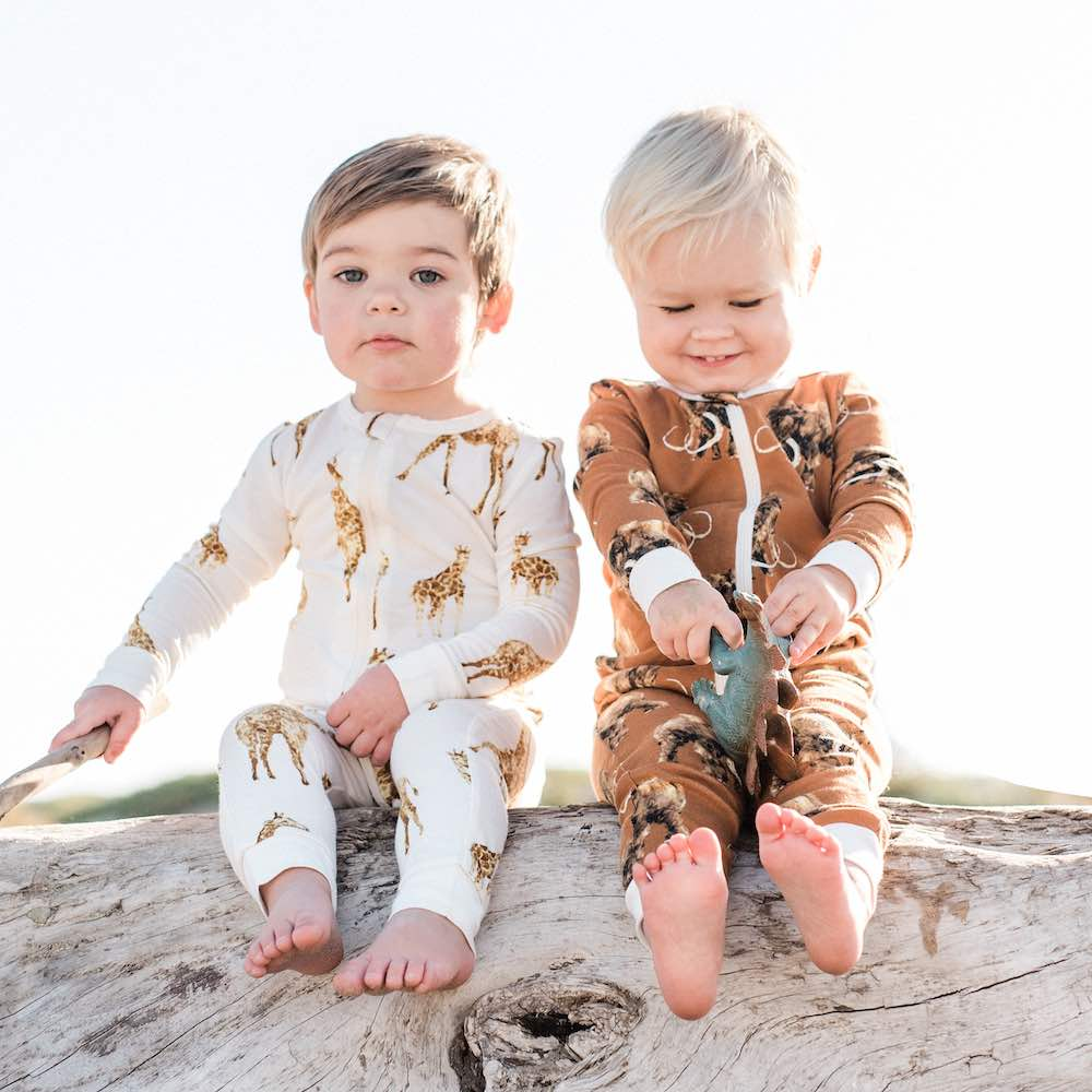 Two little baby boys wearing organic baby apparel by Milkbarn Kids consisting of a Zipper Pajama in Bamboo Orange Giraffe print and Organic Woolly Mammoth print
