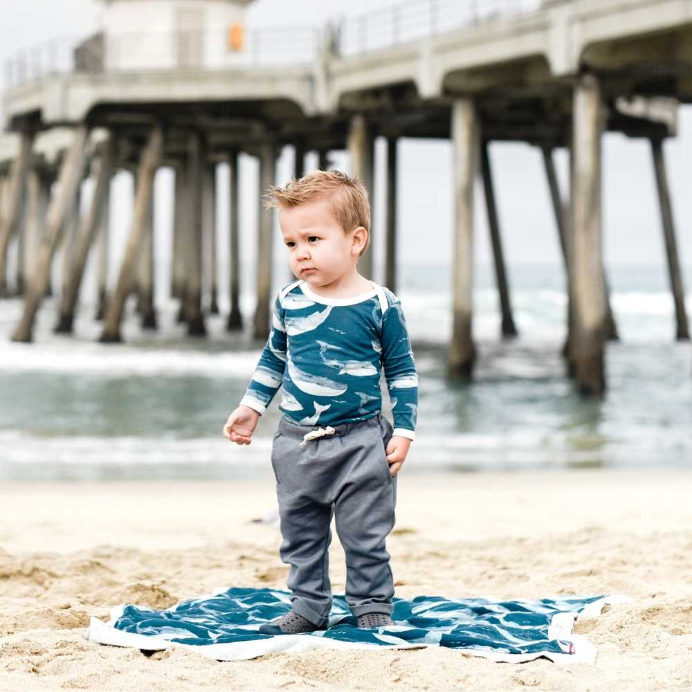 Little baby boy on the beach in in Milkbarn kids Jogger Pant in denim, a Long Sleeve One Piece in the Bamboo Blue Whale print and a Big Lovey in the Blue Whale print.