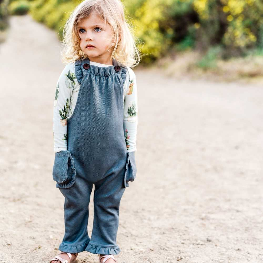 Little Girl on a Dirt Path wearing Milkbarn Kids Ruffle Overall in the Denim Fabric