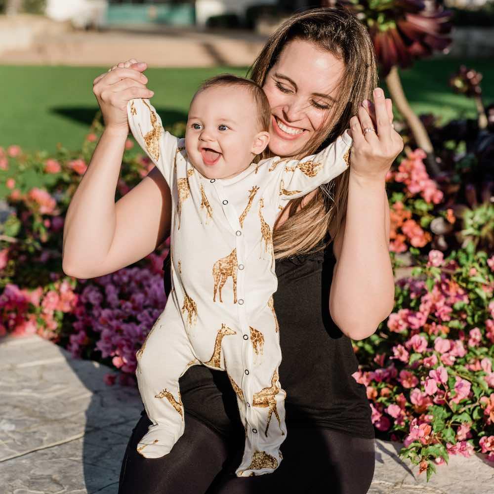 Mom and little baby in a park wearing Milkbarn Kids Footed Romper in Bamboo Orange Giraffe print