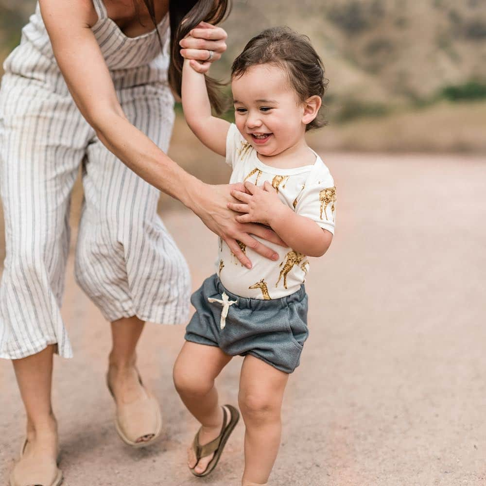 Mom and Baby Boy Wearing the Denim Pocket Bloomer and the Bamboo One Piece in the Orange Giraffe Print by Milkbarn Kids