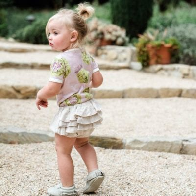Baby Girl on Rock or Crushed Granite Steps Wearing the Ruffle Bloomer in the Organic Heathered Oatmeat and the Organic One Piece in the Artichoke Print by Milkbarn Kids