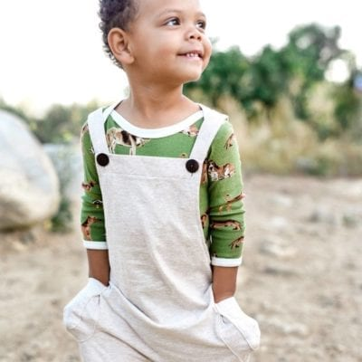 Baby Boy in a Field Wearing Organic Cotton Heathered Overalls by Milkbarn Kids