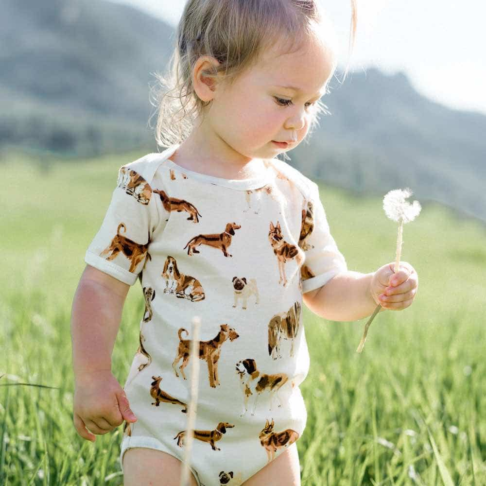 Baby Girl in a Grassy Field Wearing the Organic Cotton One Piece in the Natural Dog Print by Milkbarn Kids