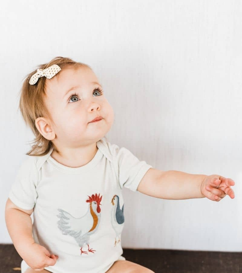 Baby Girl with a Bow Wearing the Organic Applique One Piece with the Chicken Applique by Milkbarn Kids