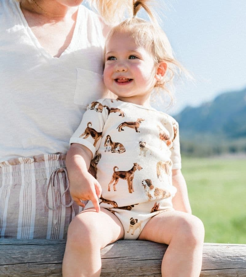 Baby Girl with her Mom by a green field wearing the Organic Cotton One Piece in the Natural Dog Print