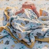 Baby Laying on Muslin Fitted Crib Sheets by Milkbarn Kids in the Butterfly Print