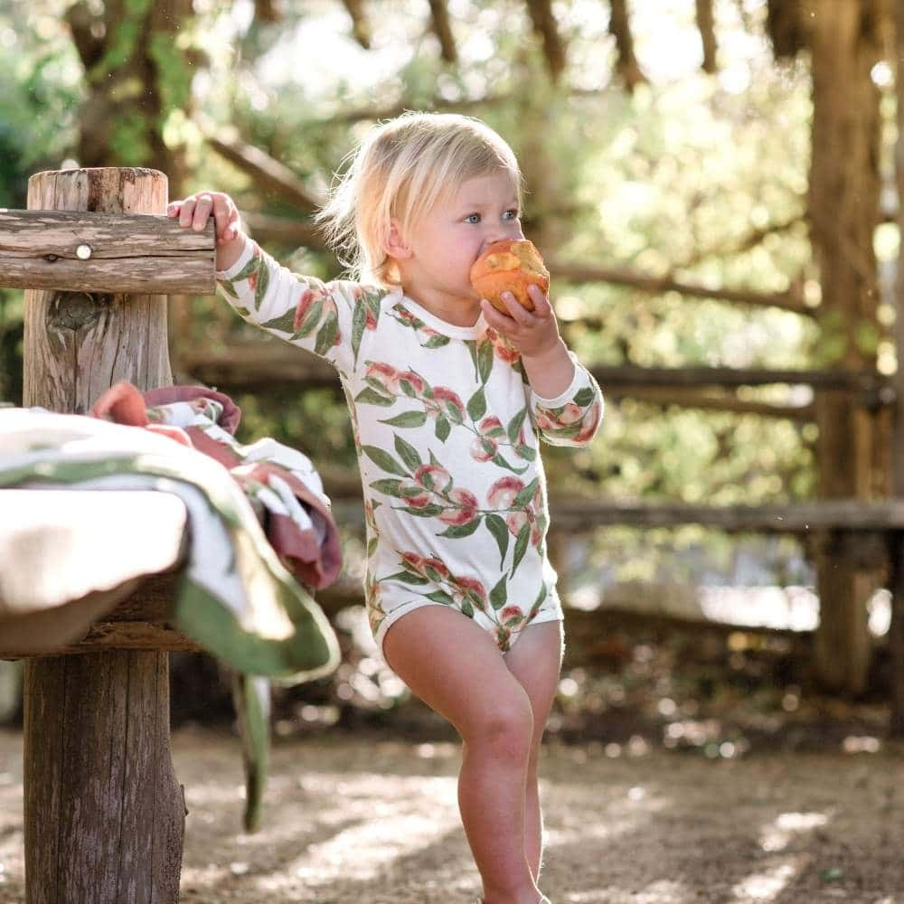 Little Baby Girl in a Park Wearing Peaches Organic Cotton Long Sleeve One Piece by Milkbarn Kids