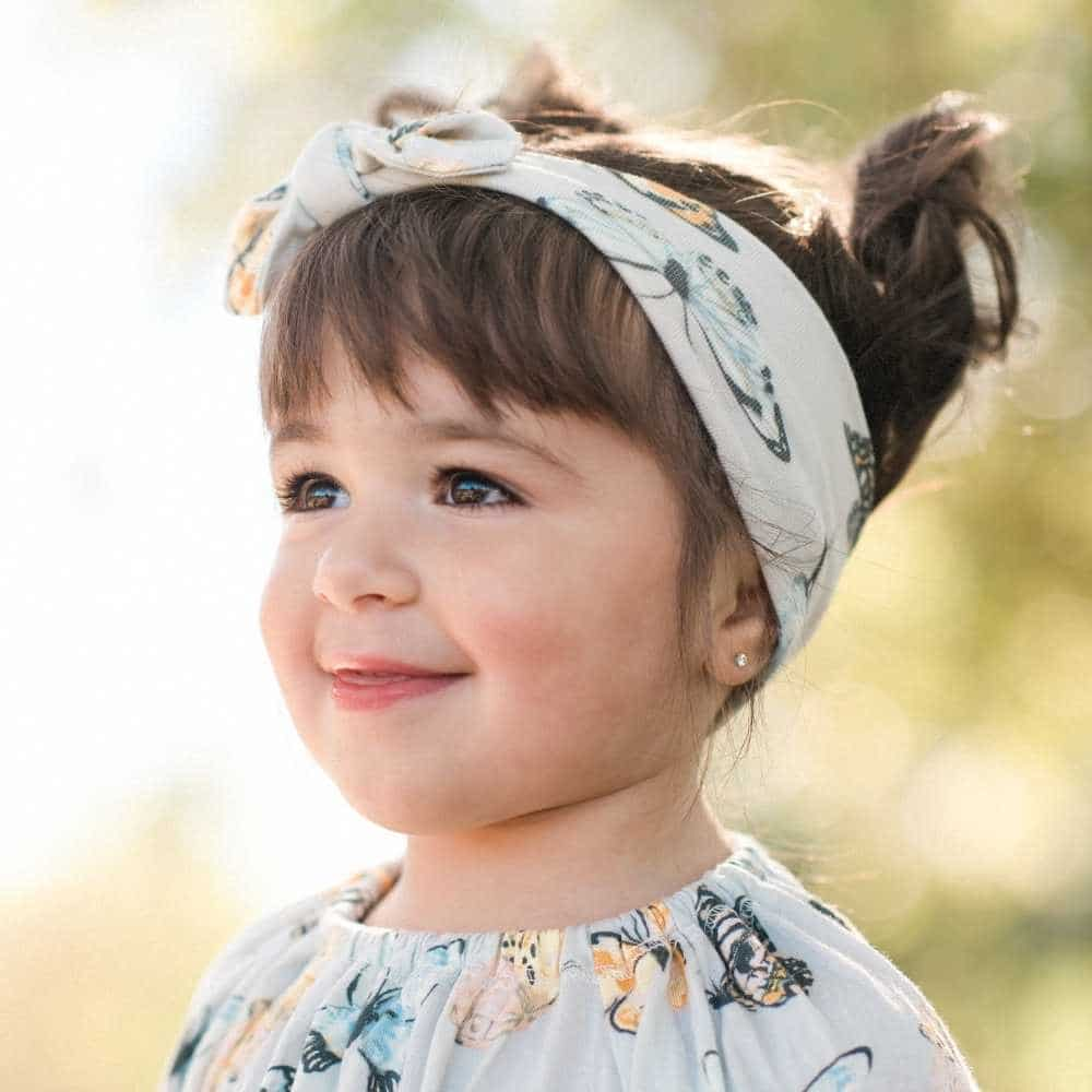 Baby Girl Wearing the Butterfly Bamboo Knotted Headband by Milkbarn Kids