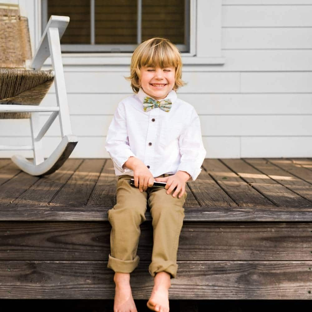 Boy Sitting on a Porch Laughing Wearing Blue Floral Bow Tie by Milkbarn Kids