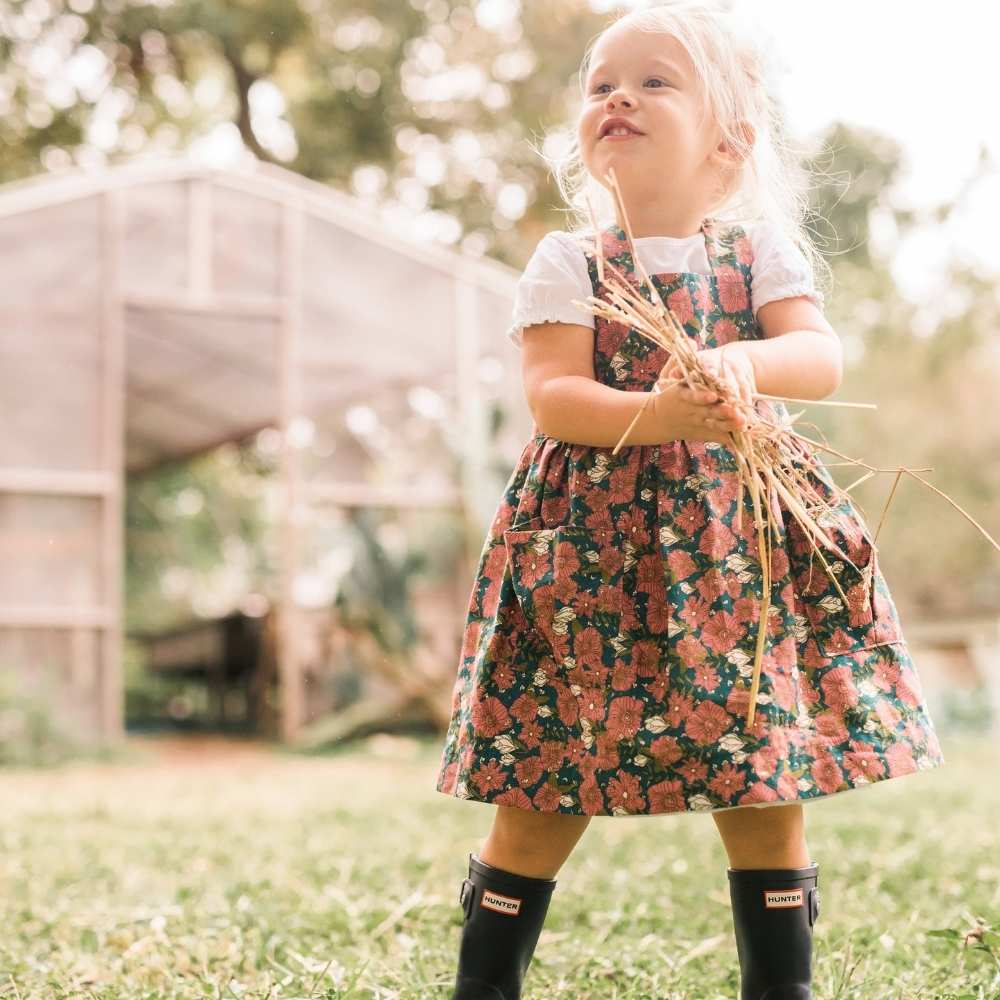 Little Girl in a garden holding hay wearing a Organic Pinafore Apron by Milkbarn Kids