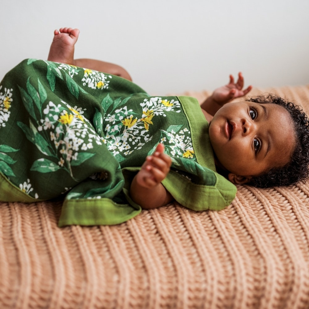Baby girl lying on a bed covered with the Green Floral Mini Lovey Security Blanket by Milkbarn Kids