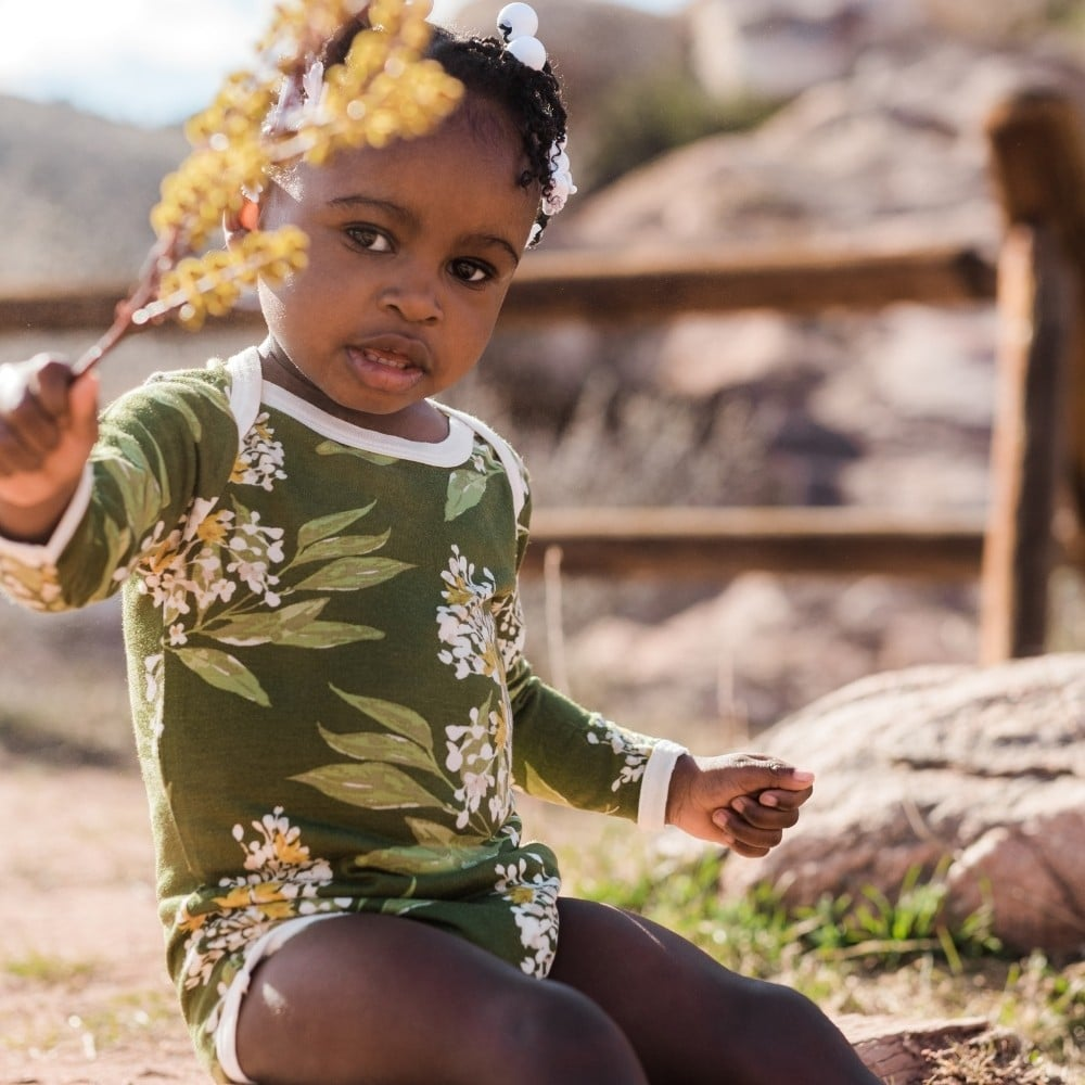 Baby Girl in a field holding yellow flowers wearing the Gren Floral Bamboo Long Sleeve One Piece by Milkbarn Kids