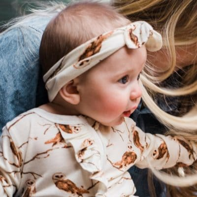 Baby girl on a Mom's lap wearing the Knotted Headband in the Owl print by Milkbarn Kids