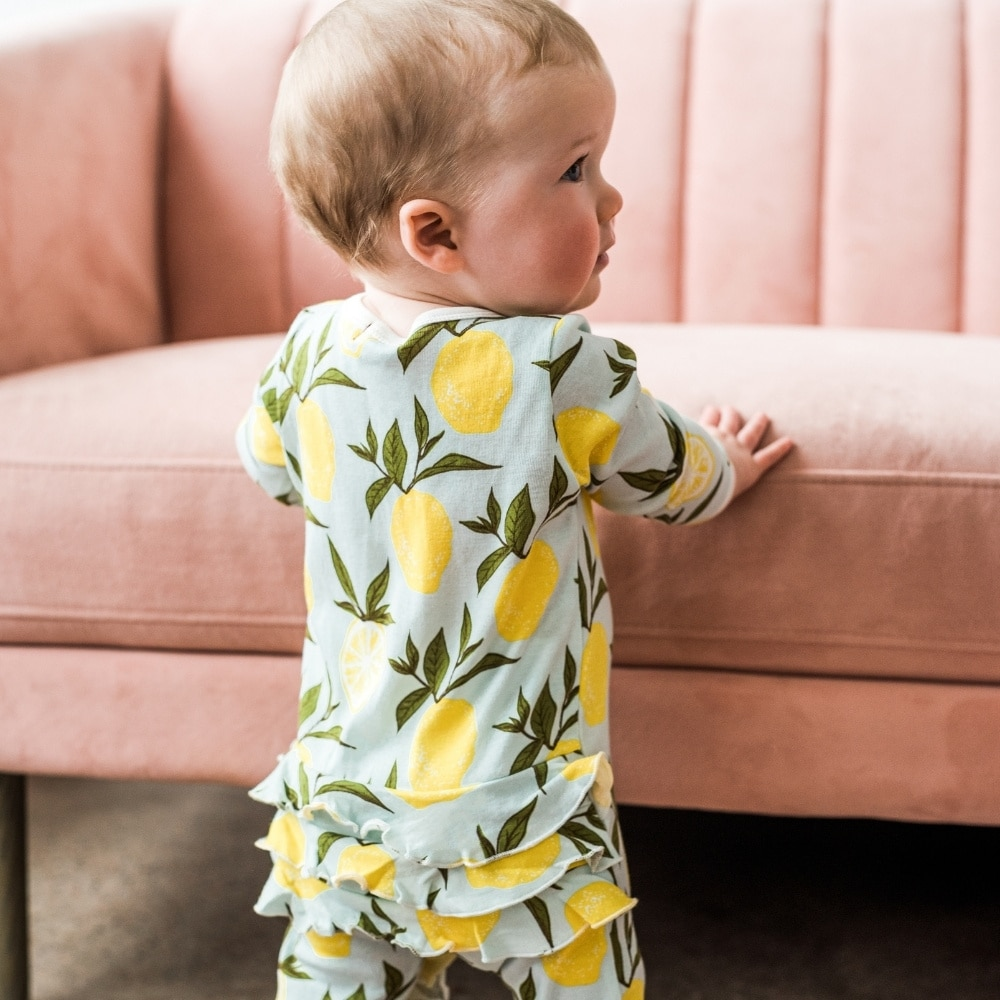 Baby girl holding herself up on a pink couch wearing the Lemon Organic Cotton Rear Ruffle Zipper Footed Romper by Milkbarn Kids
