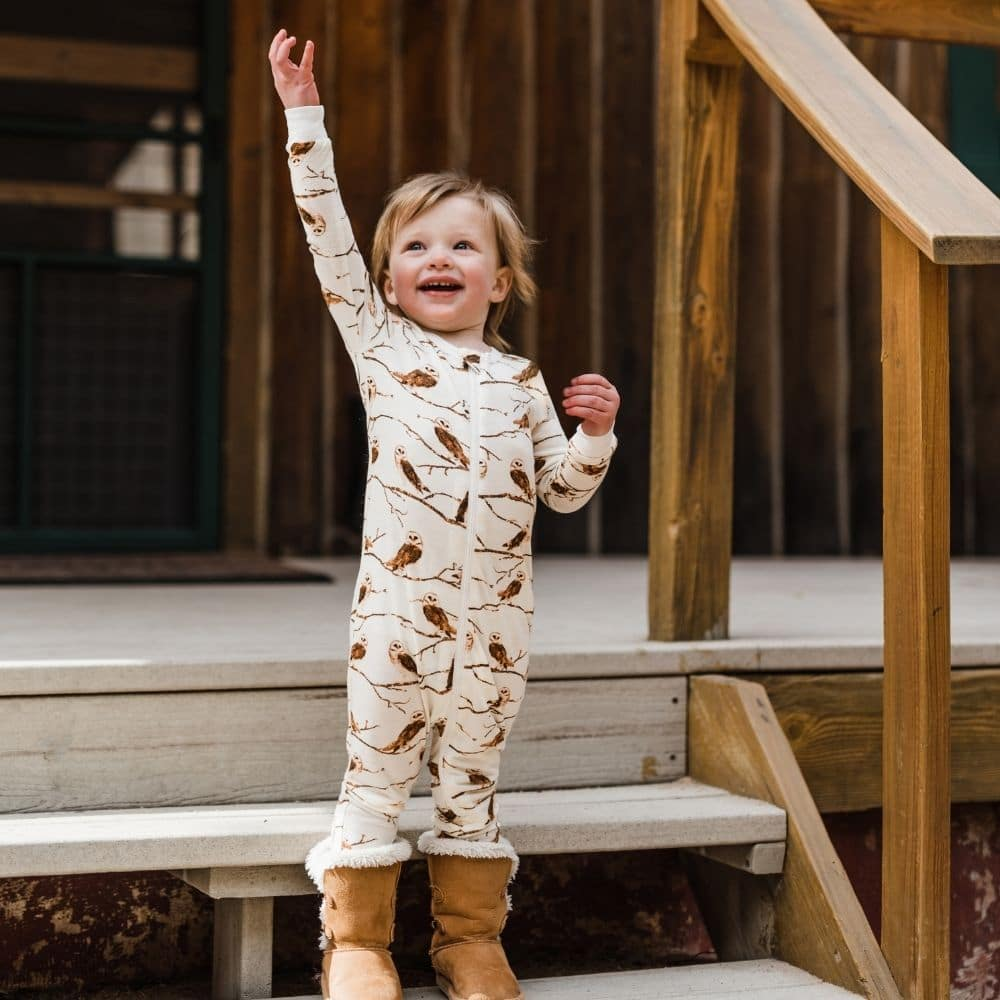 Little Boy on Cabin Steps Raising his Hand Wearing the Owl Bamboo Zipper Pajamas by Milkbarn Kids