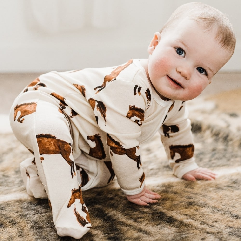Baby crawling on a horse rug wearing Natural Horse Organic Cotton Zipper Footed Romper by Milkbarn Kids