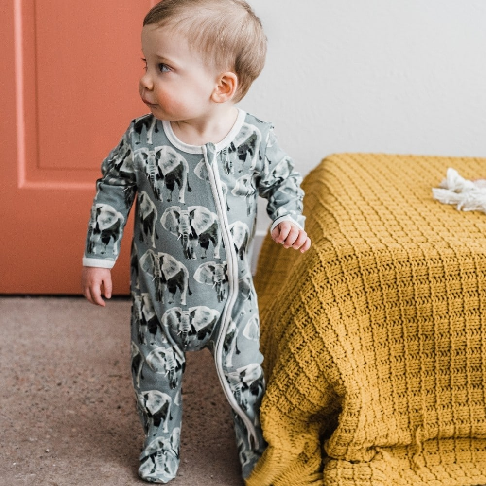 Baby boy at the foot of a bed wearing the Organic Cotton Zipper Footed Romper in the Grey Elephant print by Milkbarn Kids