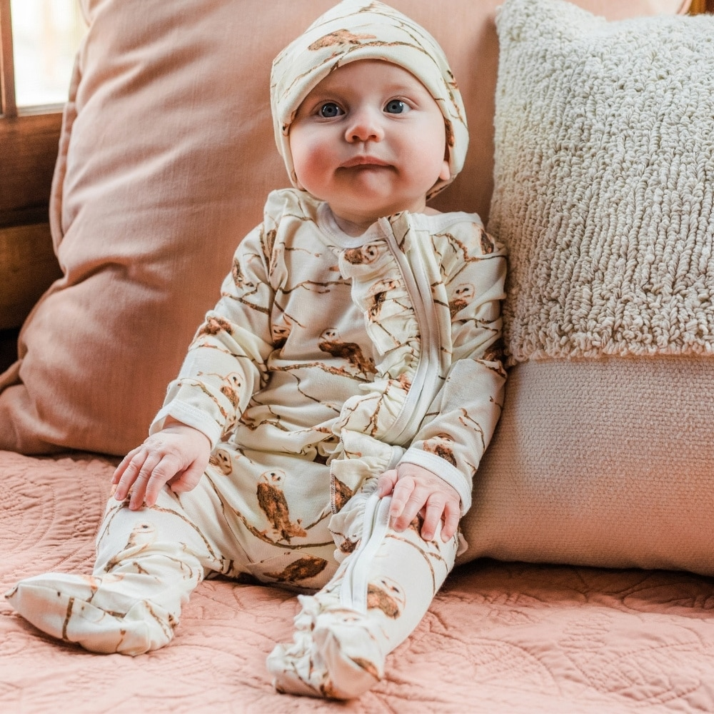 Baby propped up on a pink velvet couch and pillow wearing the owl Bamboo Ruffle Zipper Footed Romper and matching Owl Bamboo Knotted Hat by Milkbarn Kids
