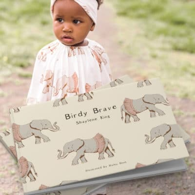 Little girl outside wearing the Tutu Elephant Bamboo Dress and Leggings with a matching headband. The print matches the children's book illustrations in Birdy Brave by Shaylene King for Milkbarn Kids