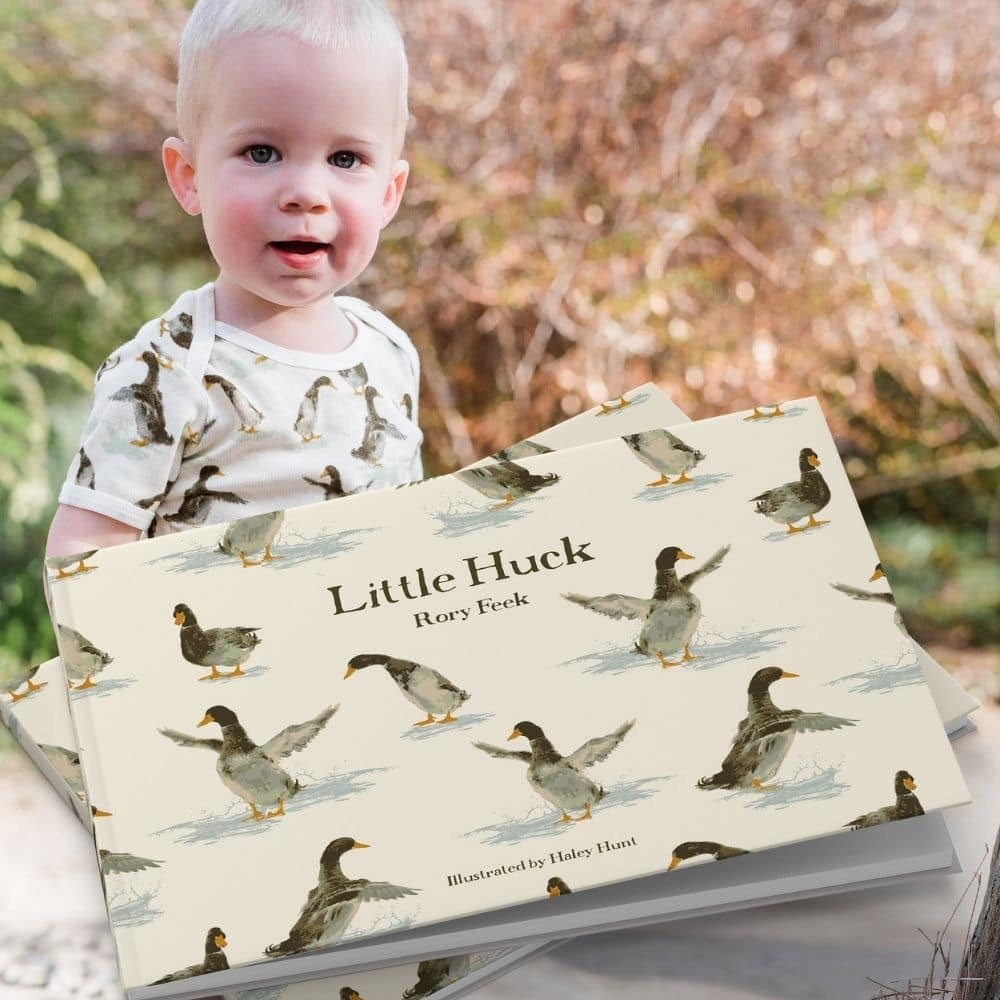 Little Boy outside in a garden wearing the duck print short sleeve one piece by Milkbarn Kids with the matching book Little Huck by Rory Feek